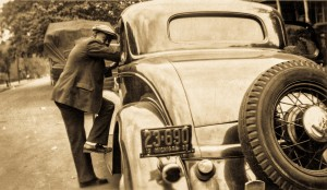 A man leans on the running board of beautiful coupe.  Michigan (1935)