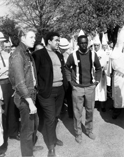 Ku Klux Klan rally.  The man on the left is Sam Shirah, and the man in the center is James Zeke Bond.  Both were members of SNCC.  Man on the right is unidentified.  Activities of these men was centered mostly in Alabama and Mississippi.  Date is approximate; true date unknown.