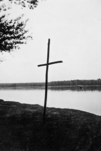 A lone cross at a lake.