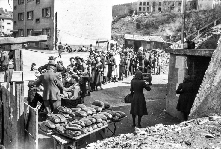 Germans line up for bread in the American Sector of post war Germany. Law 4 posted on the bunker; reinstitution of the court system in effect before Hitler.