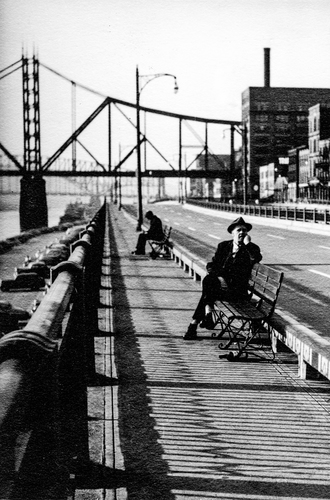 Idle men sitting along a river bank in a big city during the Great Depression.