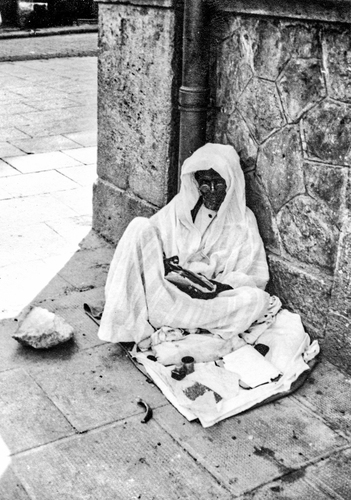 A homeless Muslim man begs on the streets of Paris c.1950.