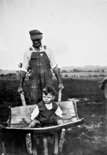 A farmer pushes his son in a homemade wheelbarrow during the Great Depression, c.1936