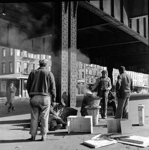 Homeless men gather around a fire to keep warm.  Date is approximate; true date unknown.
