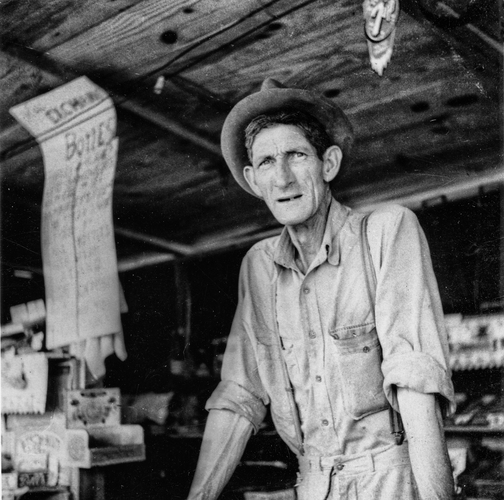 Macon, Georgia (1931). The weary, haunting stare of a Depression era shopkeeper. DPI's homage to Dorothea Lange's Ditched,
