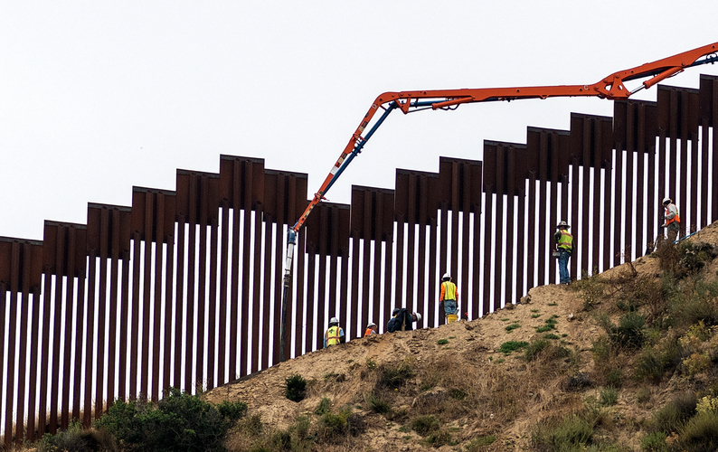 Workers pour concrete at the border fence between San Diego, California and Tijuana, Mexico.