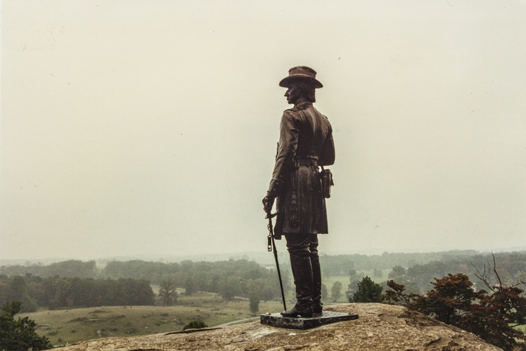 The statue of Union Brig. General Gouverneur K. Warren searches the battlefield from Little Round Top at Gettysburg.