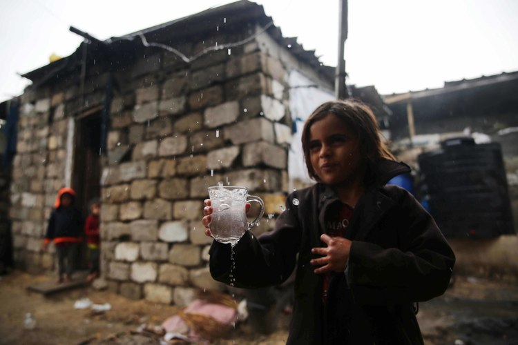 A child refills drinking water from rain in cold weather and due to the difficult conditions in the Gaza Strip, east of Khan Yunis.