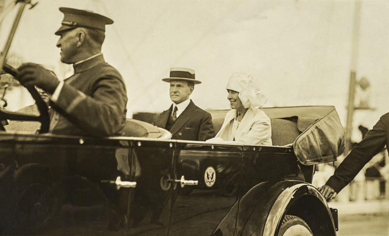 President Coolidge with his wife Grace riding in an open limousine. c.1925